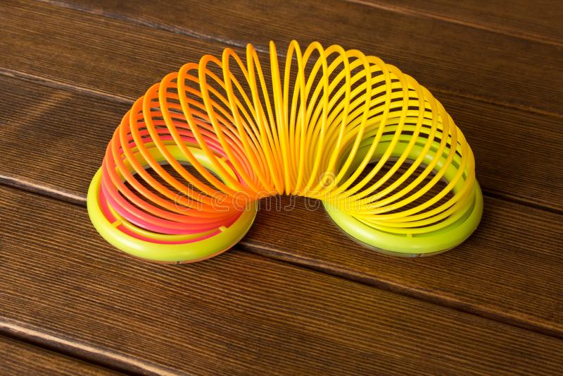 Arco-íris plástico do brinquedo em uma tabela de madeira espiral Multi-colorida para foto de stock