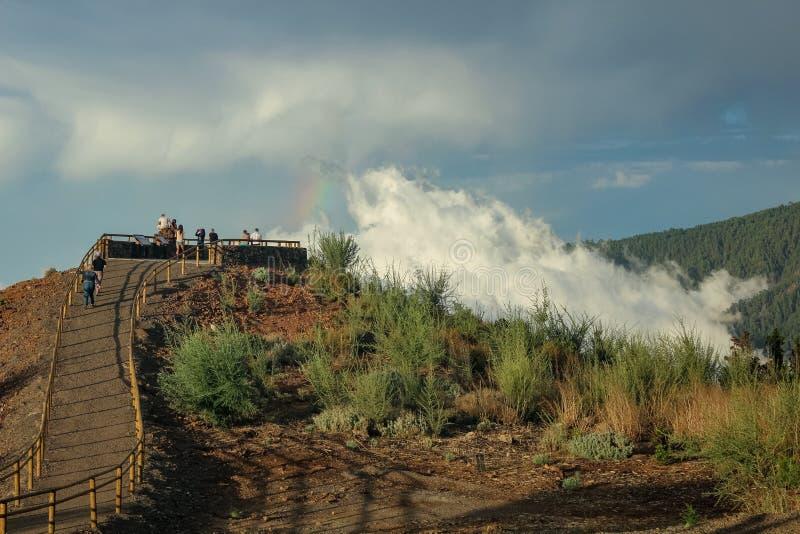 Arco-íris sobre a floresta, o fenômeno da natureza, rochas e árvores, cores brilhantes no arco-íris, chuva e céu nebuloso fotos de stock