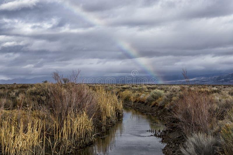 Arco-íris sobre um pântano e canal em um dia tormentoso foto de stock royalty free