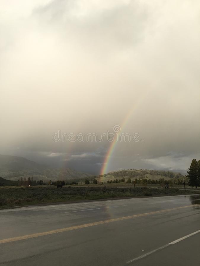 Arco-íris sobre uma estrada molhada com céus nebulosos imagens de stock royalty free