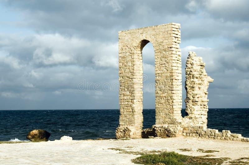 Arco antiguo - ruinas sobre la costa fotos de archivo