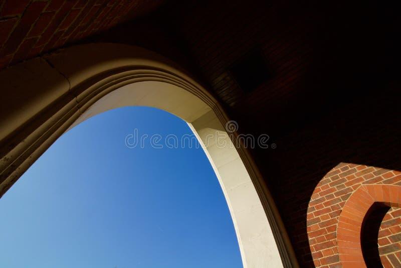 Arco bianco diretto visibile del cielo accanto a muratura - immagine immagini stock