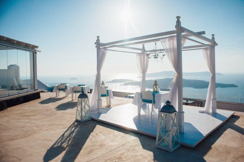 Arco bianco per una cerimonia di nozze all'aperto con le lanterne e una piattaforma con mobilia bianca sui precedenti del mare, fotografie stock libere da diritti