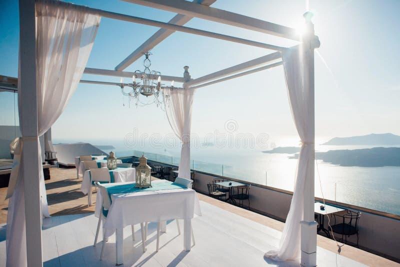 Arco bianco per una cerimonia di nozze all'aperto con le lanterne e una piattaforma con mobilia bianca sui precedenti del mare, immagini stock