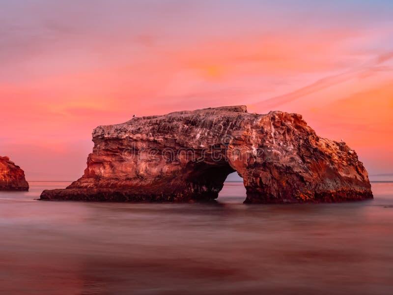 Arco bonito da rocha contra o céu colorido do por do sol foto de stock royalty free