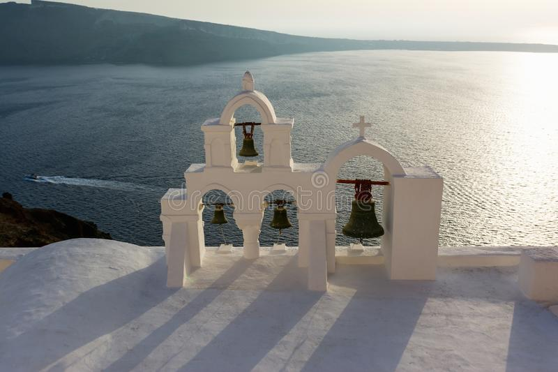 Arco con la cruz y las campanas de la iglesia blanca griega tradicional en el pueblo de Oia, isla de Santorini, Grecia imagen de archivo