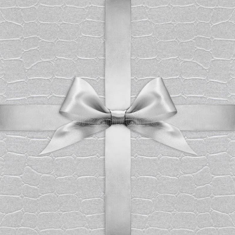Arco d'argento brillante del nastro del raso sull'argento fotografia stock libera da diritti