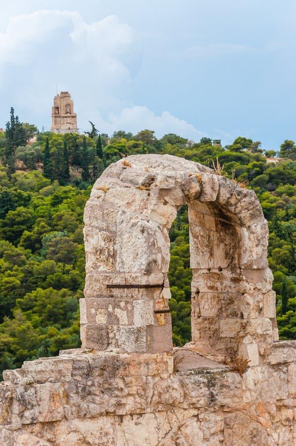 Arco da pedra da acrópole com a vista no monumento famoso de Philopappos na parte superior do monte em Atenas, Grécia foto de stock royalty free