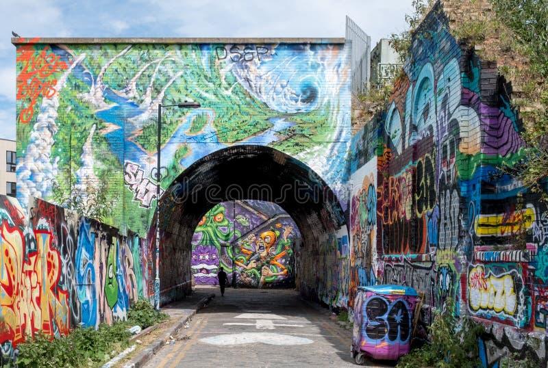 Arco da rua de Pedley, Shoreditch, Londres do leste Corredor pedestre sob a linha railway perto da pista do tijolo, coberta em gr imagens de stock royalty free