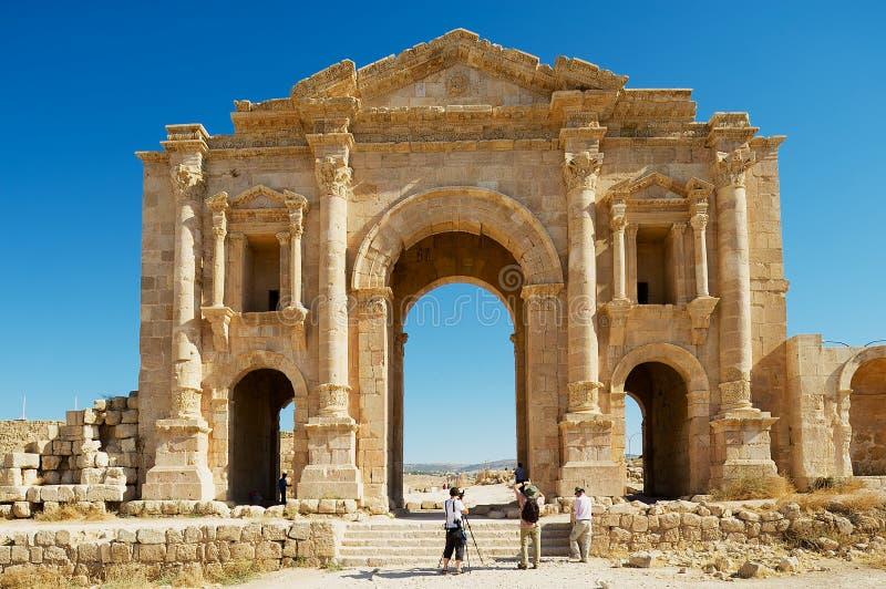 Arco da visita dos turistas de Hadrian na cidade romana antiga de Gerasa em Jerash, Jordânia imagens de stock