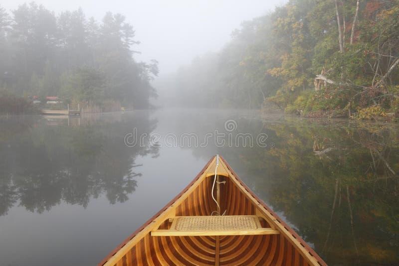 Arco de la canoa en Misty Autumn River imagen de archivo