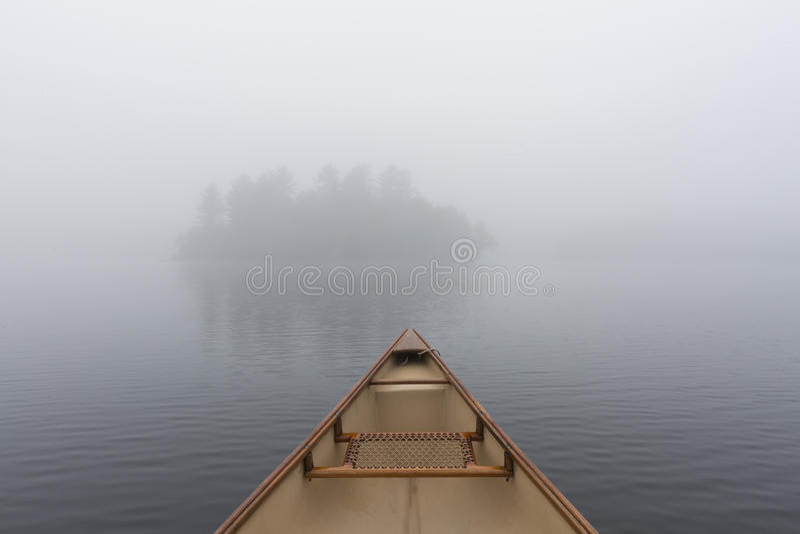 Arco de la canoa en un lago Ontario brumoso, Canadá foto de archivo