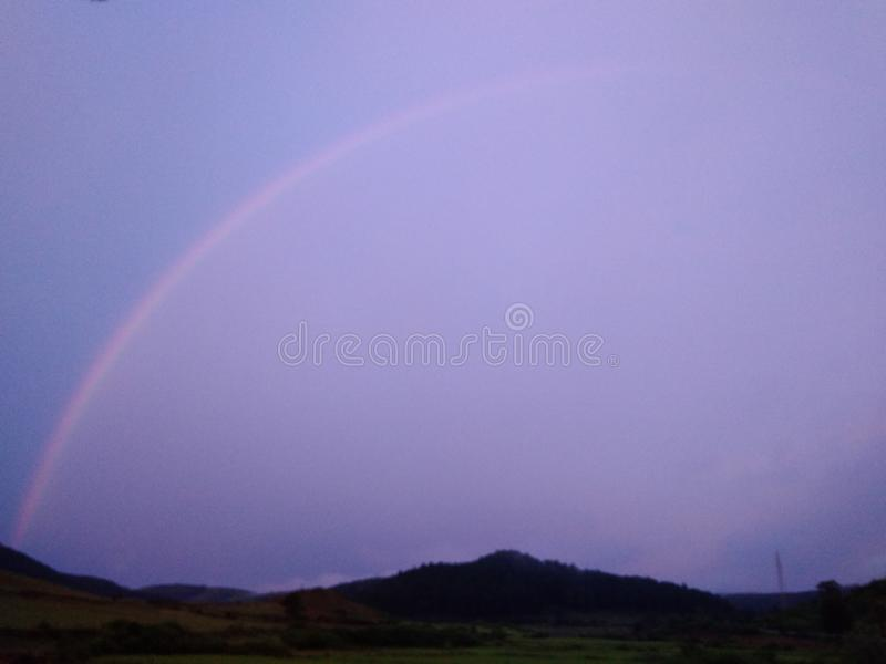Arco de la lluvia en la estación de la lluvia y hojas claras del cielo y verdes foto de archivo libre de regalías