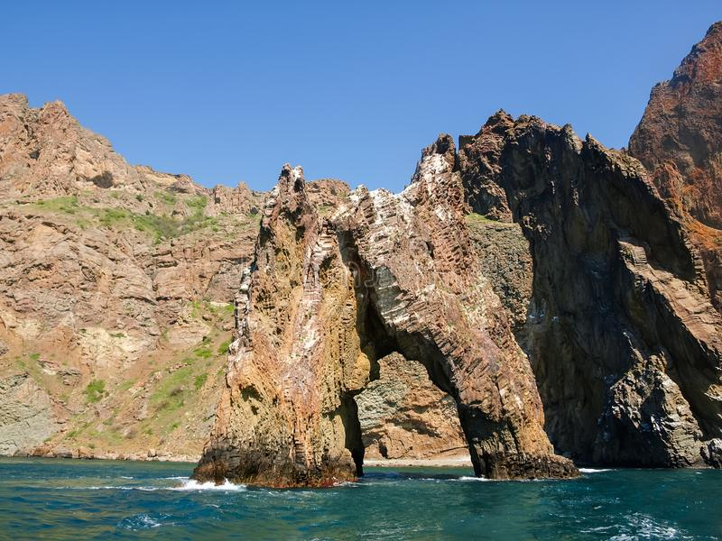 Arco de la roca del origen volcánico cerca de la orilla de mar imagen de archivo libre de regalías