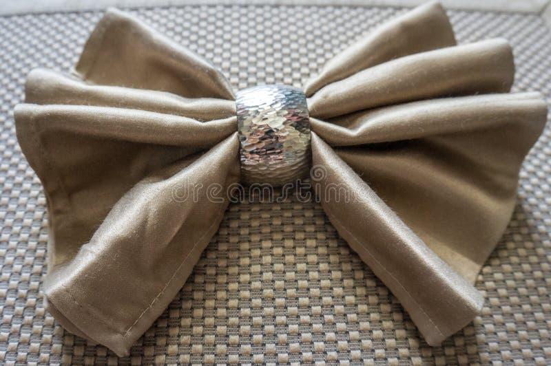 Arco de oro de la servilleta con el plegamiento de lujo del anillo de plata para el día de fiesta foto de archivo libre de regalías