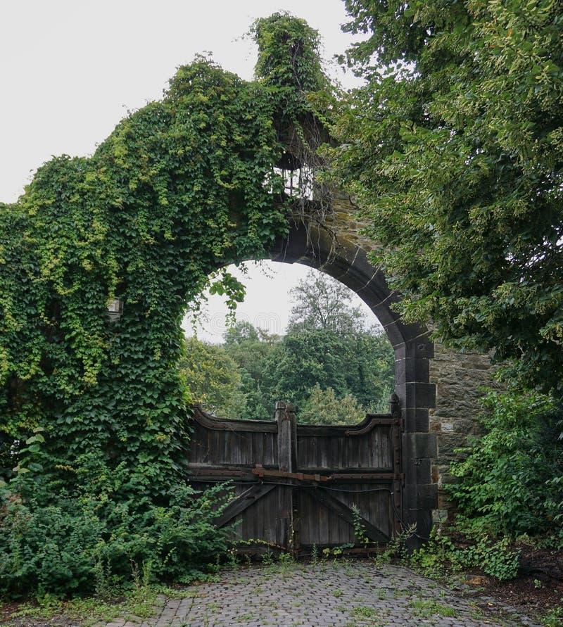 Arco de pedra velho com portas de madeira fotografia de stock