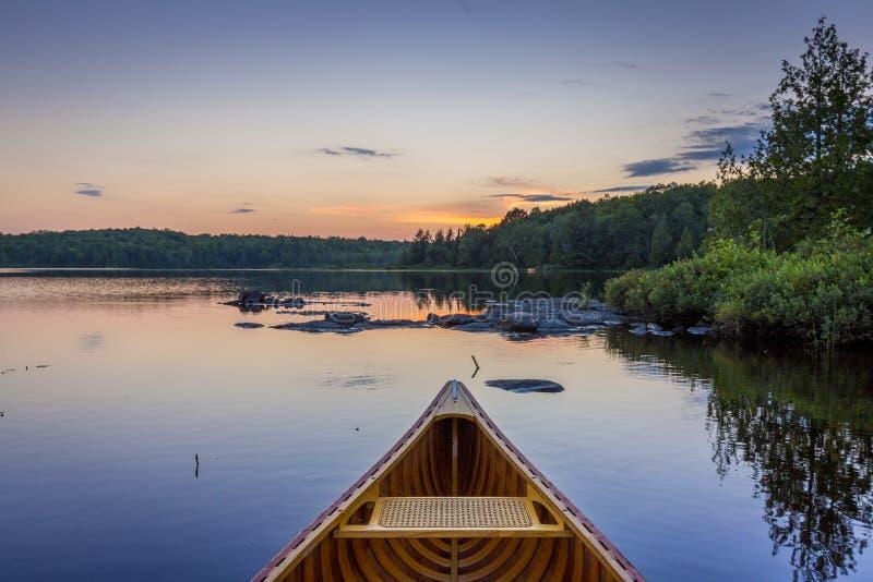 Arco de una canoa del cedro en un lago en la puesta del sol - Ontario, Canadá foto de archivo
