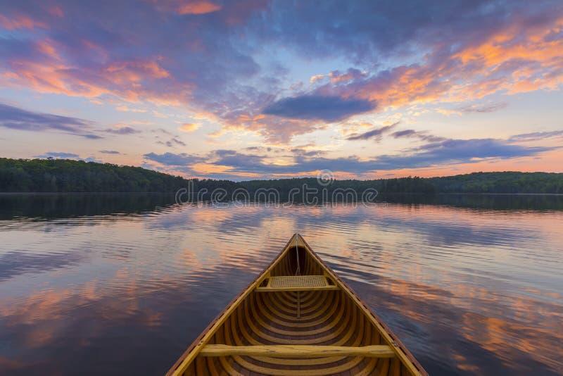 Arco de una canoa del cedro en un lago en la puesta del sol - Ontario, Canadá imagen de archivo