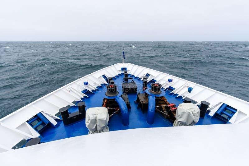 Arco de una nave grande del azul y blanca que navega el océano tranquilo hacia el horizonte imagen de archivo