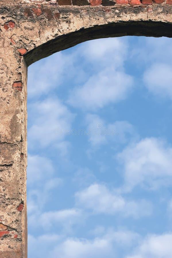 Arco della porta del portone del granaio e cielo, primo piano della parete di pietra, fondo bianco luminoso verticale dello spazi fotografia stock