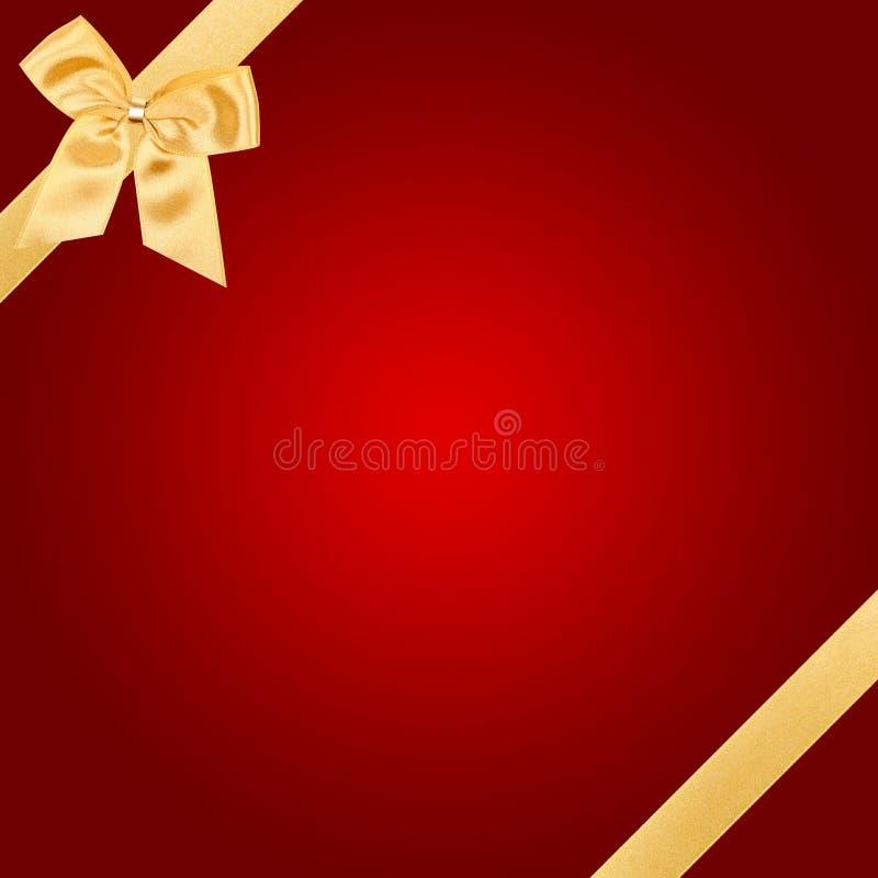 Arco di natale dell'oro sulla scheda rossa immagine stock libera da diritti