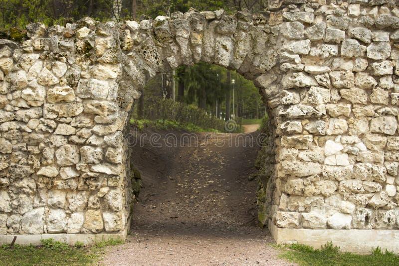 Arco di pietra, tetto semicircolare del passaggio in una vecchia parete di pietra, apertura dell'entrata della botola la grotta immagini stock libere da diritti