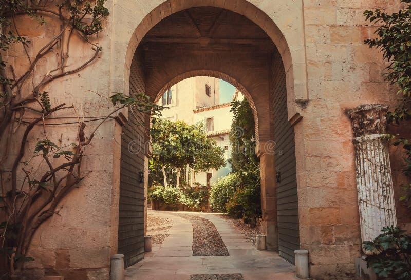 Arco di pietra tradizionale in cortile con i plansts di vecchie case, Andalusia Scena rurale a Cordova, Spagna fotografie stock
