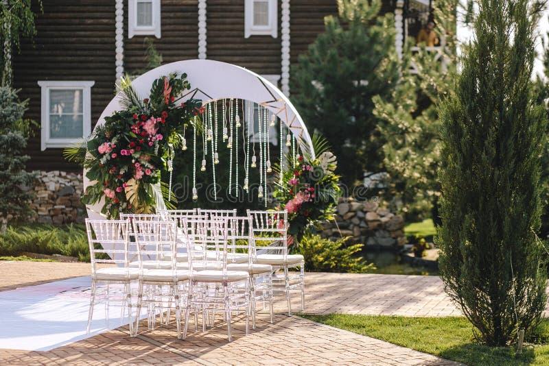 Arco do casamento sob a forma de uma lua branca com composições florais em um estilo tropical com folhas de um monstro decorado c foto de stock