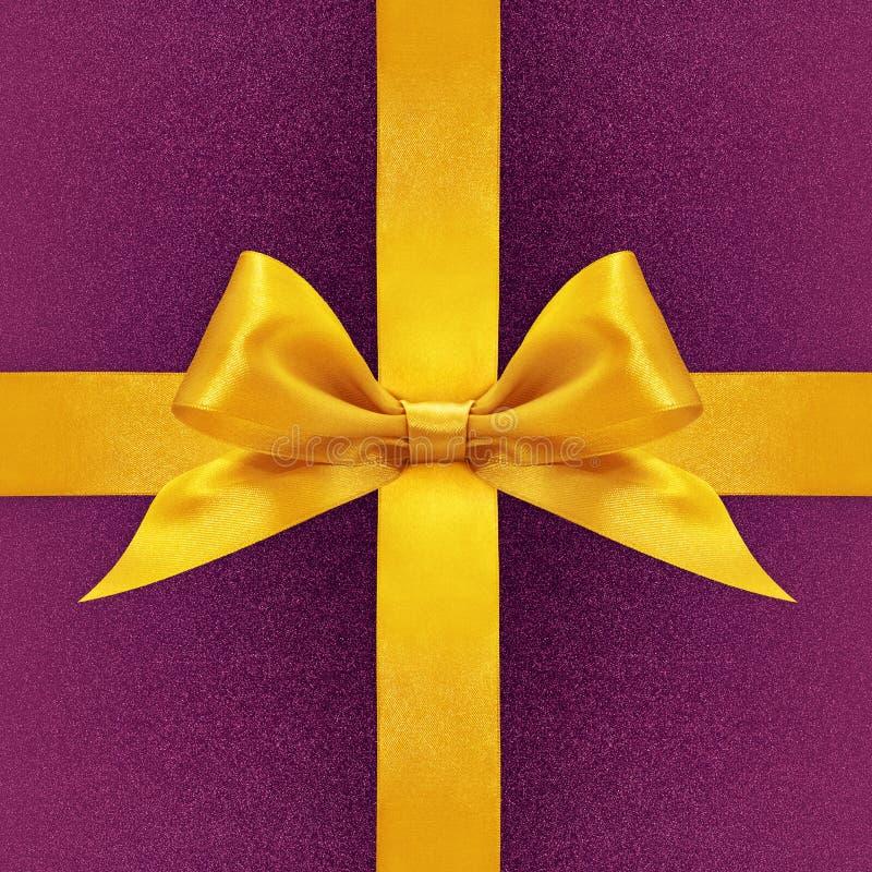 Arco dorato brillante del nastro del raso sulla porpora fotografie stock libere da diritti