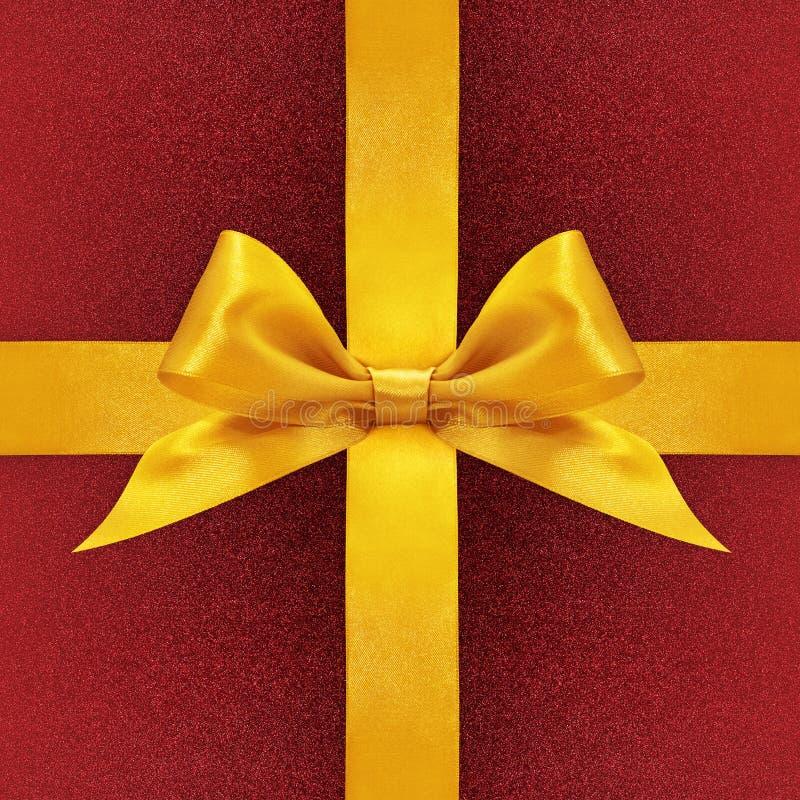 Arco dorato del nastro del raso su fondo rosso immagini stock