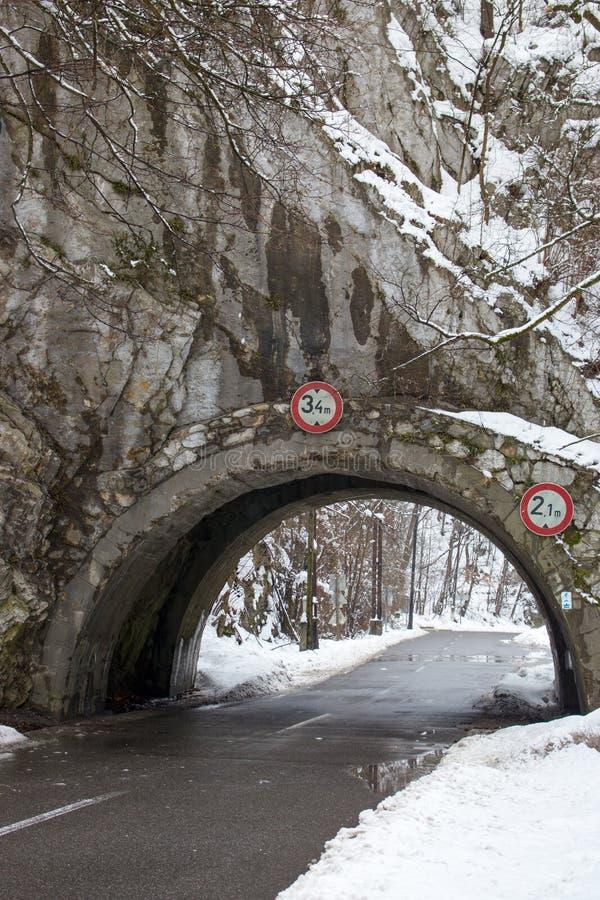 Arco e estrada nas montanhas na floresta do inverno, Hungria Arco medieval na montanha Estrada na queda de neve do inverno Estrad fotos de stock royalty free