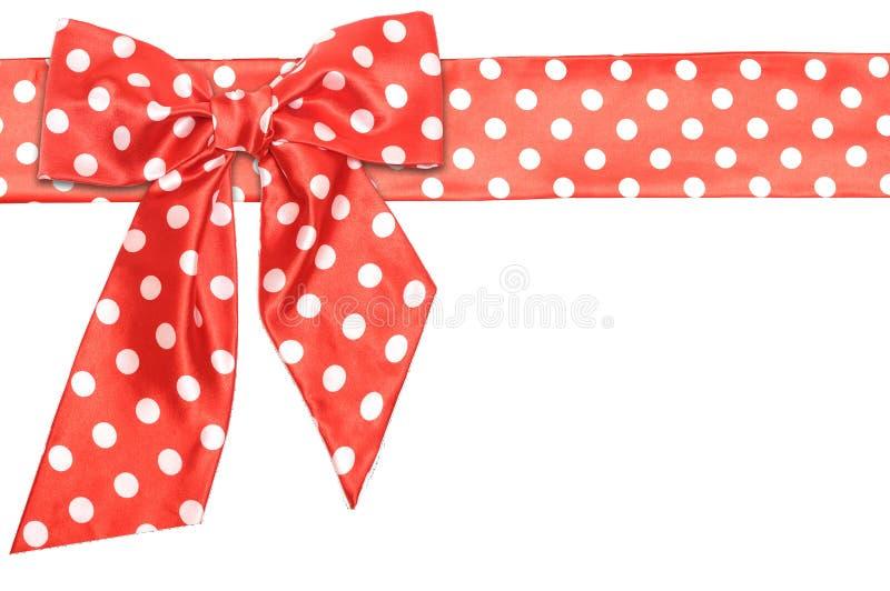 Arco e nastro rossi punteggiati del regalo del raso fotografia stock
