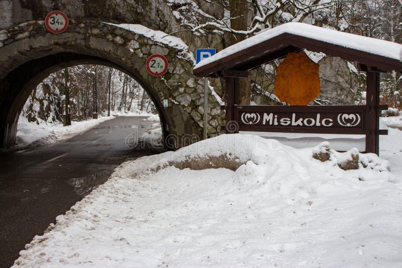 Arco e strada in montagne nella foresta di inverno, Miskolc, Ungheria Segnale stradale di Miskolc ed arco medievale in montagna S fotografia stock