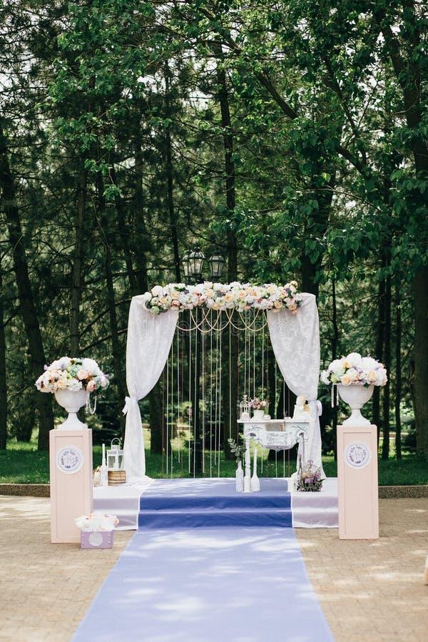 Arco elegante clásico adornado con los floreros blancos del paño con las flores, alfombra púrpura de la boda en el fondo del imágenes de archivo libres de regalías