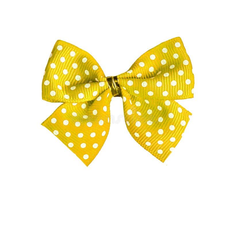 Arco giallo del nastro del tessuto con il isolat bianco del modello di pois immagini stock libere da diritti