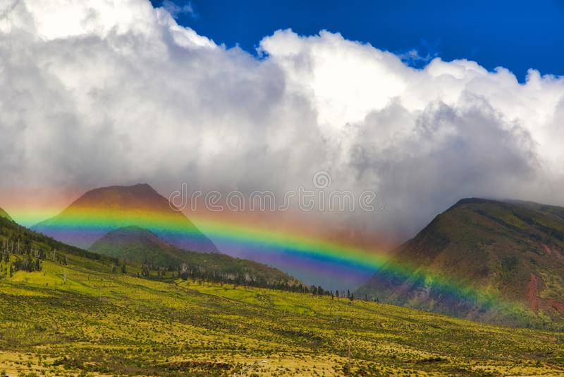 Arco iris brillante sobre las monta?as del oeste enormes de Maui imagen de archivo