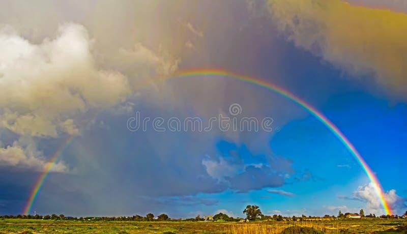 Arco iris completo con el cielo azul nublado fotos de archivo libres de regalías