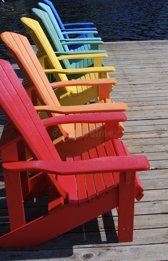 Arco iris de sillas coloreadas en el muelle en verano fotografía de archivo