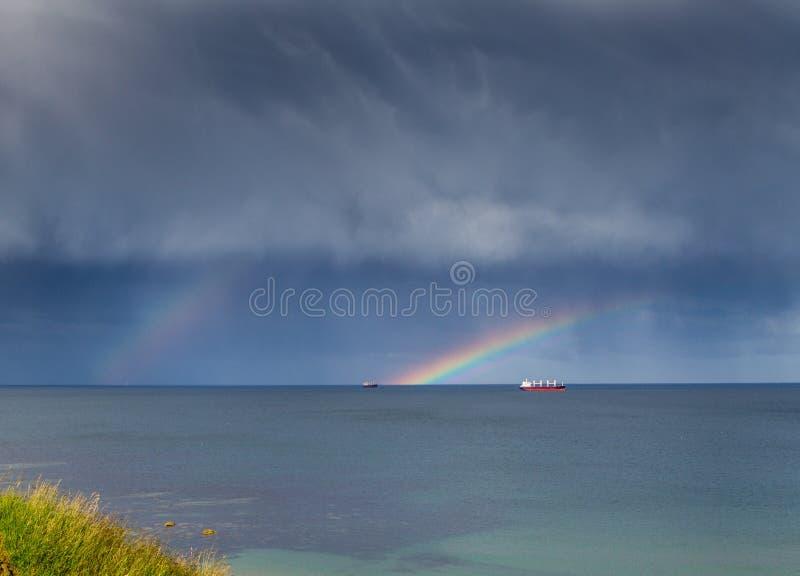 Arco iris doble hacia fuera en el mar sobre algunos barcos foto de archivo
