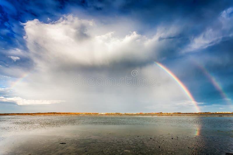 Arco iris doble lleno sobre un lago fotografía de archivo