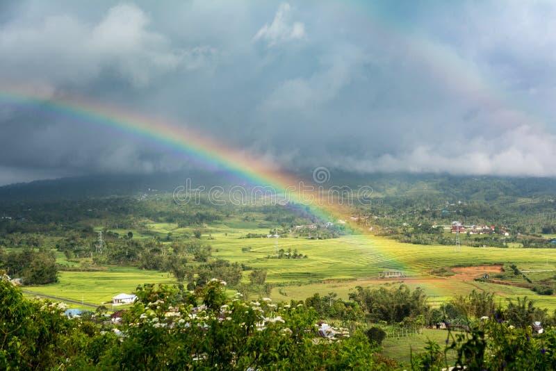 Arco iris doble sobre campo con un fondo de la tormenta Ruteng, fotos de archivo libres de regalías