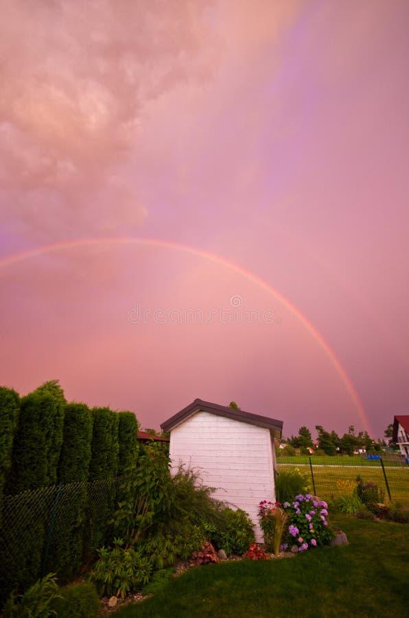 Arco iris doble sobre un jardín en color rosado imágenes de archivo libres de regalías