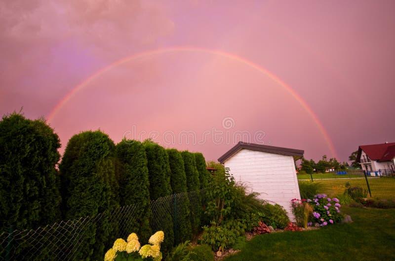 Arco iris doble sobre un jardín en color rosado foto de archivo libre de regalías