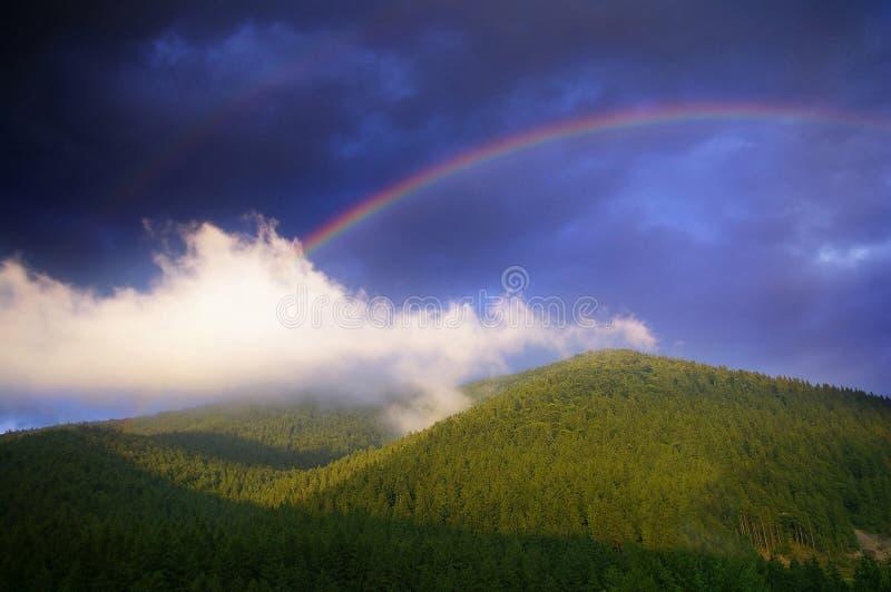 Arco iris en el cielo azul sobre el bosque y las montañas verdes fotografía de archivo libre de regalías