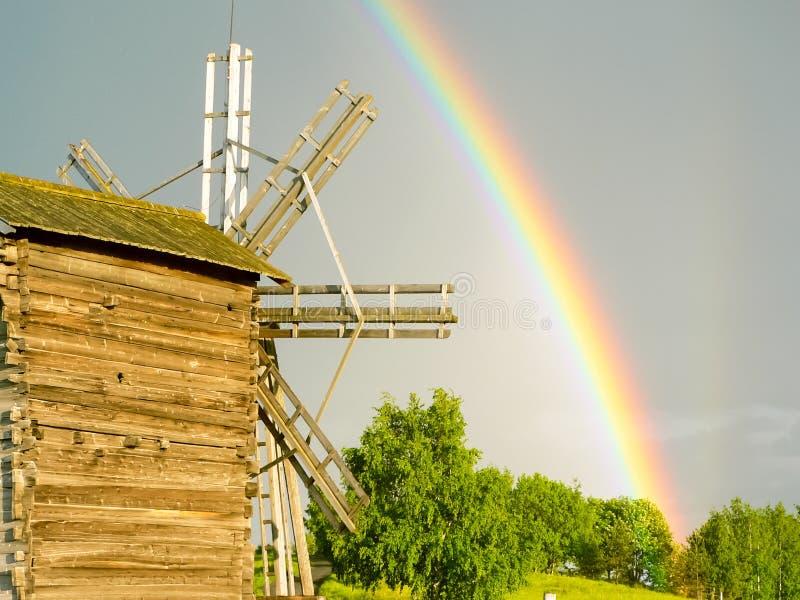 Arco iris en el fondo de un molino de viento fotografía de archivo