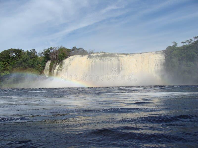 Arco iris en la laguna en frente las cascadas foto de archivo libre de regalías