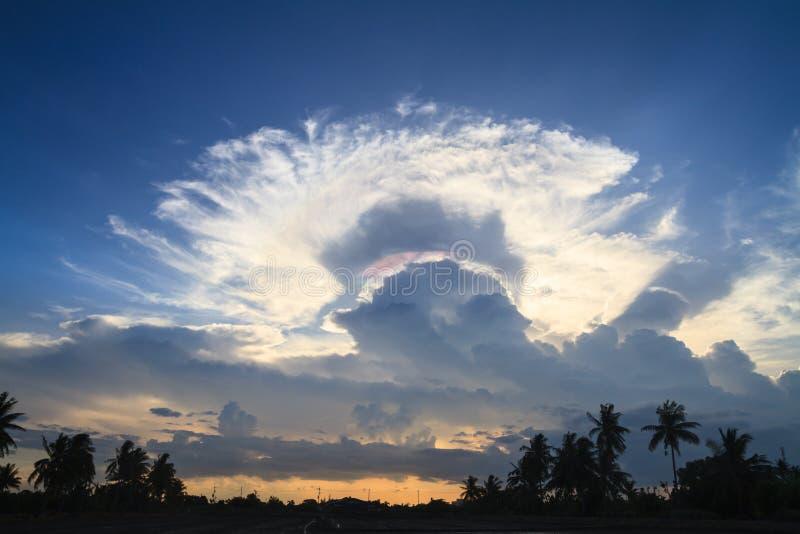 Arco iris entre hueco de dos nubes en puesta del sol foto de archivo