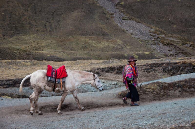 ARCO IRIS MOUNTAINES, PERÚ - 8 DE OCTUBRE DE 2016: El hombre peruano nativo que lleva la ropa y el sombrero tradicionales con su  foto de archivo libre de regalías