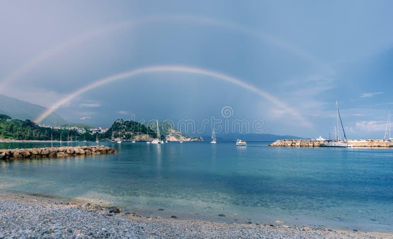 Arco iris sobre el mar y la isla con los yates y los barcos en el agua fotografía de archivo