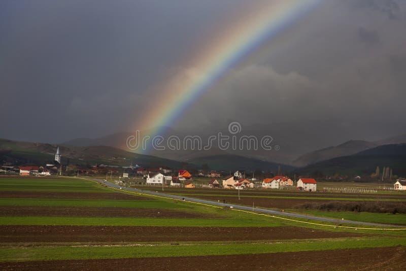 Arco iris sobre pueblo y tierras de labrantío imagen de archivo